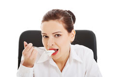 Beautiful young business woman eating yoghurt. Royalty Free Stock Image