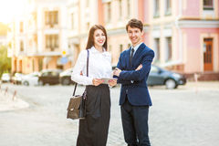 Beautiful young business woman and handsome businessman in formal suits are using a digital tablet in city background Royalty Free Stock Photo