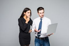 Beautiful young business woman and handsome businessman in formal suits are using a laptop, talking and smiling, standing before g Stock Image