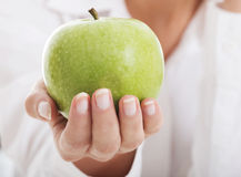 Beautiful young business woman holding an apple. Stock Images