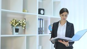 Beautiful young business woman holding folder in bright office at office.  stock video