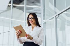 Beautiful young business woman looking at her tablet in a large corporate building stock photo
