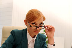 Beautiful young business woman looking over her glasses at camer Stock Image