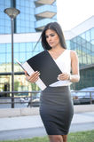 Beautiful young business woman looking at work papers. Outdoors Royalty Free Stock Photo