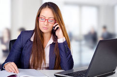 Beautiful young business woman making a phone call in her office. Beautiful young business woman making a phone call from her office stock images