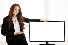 Beautiful young business woman near television screen display with copy space for additional text or graphic.  royalty free stock photos