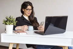Beautiful young business woman in office with phone in the hands Royalty Free Stock Photography