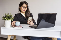 Beautiful young business woman in office with phone in the hands Royalty Free Stock Photos