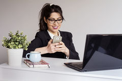 Beautiful young business woman in office with phone in the hands Stock Photo
