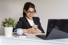 Beautiful young business woman in office with phone in the hands Stock Images
