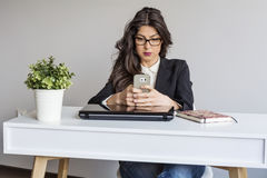 Beautiful young business woman in office with phone in the hands Royalty Free Stock Image