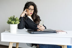 Beautiful young business woman in office with phone in the hands Stock Photography