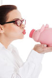 Beautiful young business woman with piggy-bank. Stock Images