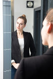 Beautiful young business woman preparing herself for confident morning routine Stock Photo