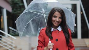 Beautiful young business woman in red coat walking on the street in rainy weather, smiling, holding umbrella. She stock footage