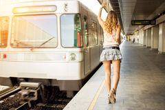 Beautiful young business woman running after train Stock Photo
