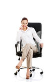 Beautiful young business woman sitting on a chair. Royalty Free Stock Photo