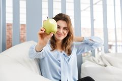 Beautiful young business woman sitting on a couch royalty free stock photos