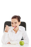 Beautiful young business woman sitting and eating apple and yogh Royalty Free Stock Images
