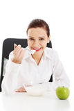 Beautiful young business woman sitting and eating apple and yogh Stock Photos