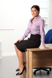 Beautiful young business woman sitting on office d Royalty Free Stock Images