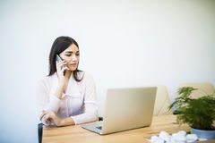 Beautiful young business woman sitting at office desk and talking on cell phone Stock Photos