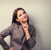 Beautiful young business woman in suit thinking and looking up. Royalty Free Stock Image