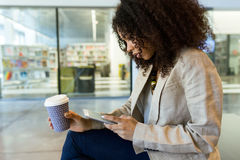 Beautiful young business woman using her digital tablet and drinking coffee in a hallway of her company. Stock Photography