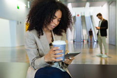 Beautiful young business woman using her digital tablet and drinking coffee in a hallway of her company. Royalty Free Stock Images