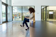 Beautiful young business woman using her digital tablet in a hallway of her company. Royalty Free Stock Images