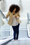 Beautiful young business woman using her mobile phone on escalator. Royalty Free Stock Photos