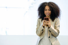Beautiful young business woman using her mobile phone in a hallway of her company. Portrait of beautiful young business woman using her mobile phone in a Stock Photo