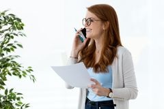 Beautiful young business woman using her mobile phone and reviewing papers in the office. Royalty Free Stock Image