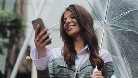Beautiful young business woman using smartphone on the street in rainy weather, smiling, holding umbrella, communication stock video footage