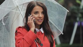 Beautiful young business woman using smartphone on the street in rainy weather, smiling, holding umbrella, dialing stock footage