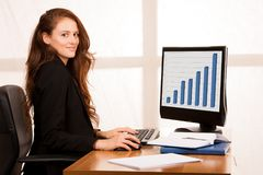 Beautiful young business woman work at her desk in the office wi. Th window in the background Royalty Free Stock Photo