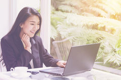 Beautiful young business woman working with laptop ,looking screen With gesture of rejoicing, shock, surprise emotion Royalty Free Stock Photo