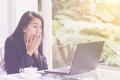 Beautiful young business woman working with laptop ,looking screen With gesture of rejoicing, shock, surprise emotion Stock Photo