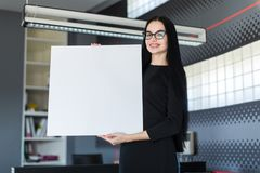 Beautiful young businesswoman in black dress and glasses hold empty poster Royalty Free Stock Photography