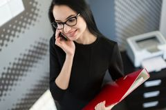 Beautiful young businesswoman in black dress and glasses hold paper folder royalty free stock photos