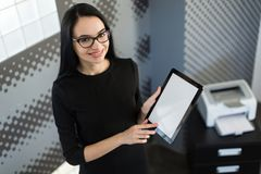 Beautiful young businesswoman in black dress and glasses hold paper folder and show tablet Royalty Free Stock Image