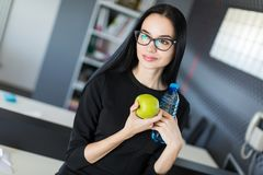 Beautiful young businesswoman in black dress and glasses sit on table in the office and hold green apple and bottle Royalty Free Stock Photography