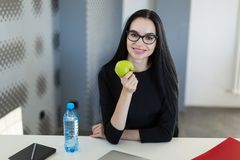 Beautiful young businesswoman in black dress and glasses sit at the table in the office and hold green apple Stock Photos