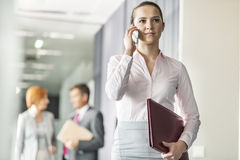 Beautiful young businesswoman on call with colleagues in background at office corridor Stock Photos