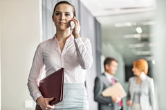 Beautiful young businesswoman on call with colleagues in background at office corridor Stock Image