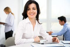 Businesswoman with colleagues. Beautiful young businesswoman with colleagues in modern office Stock Photos