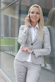 Beautiful young businesswoman conversing on cell phone while leaning on glass wall Royalty Free Stock Images