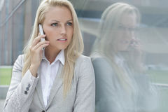 Beautiful young businesswoman conversing on cell phone while looking away by glass wall Royalty Free Stock Photography