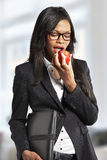 Beautiful young businesswoman eating apple Stock Images