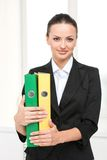 Beautiful young businesswoman holding binder. Royalty Free Stock Image